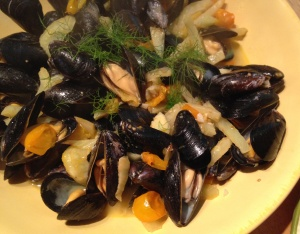 Use a ladle to scoop up a number of mussels (with their shells) and broth.